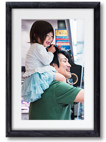 Image of a father and child reaching into a refrigeration display case in a grocery store.