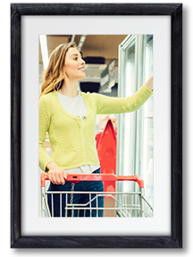 Image of a woman opening a refrigeration display case while grocery shopping