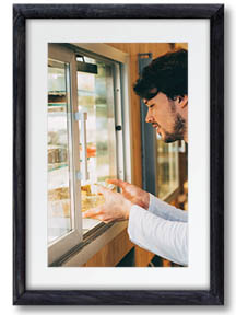 Image of a man placing food in a refrigeration display case