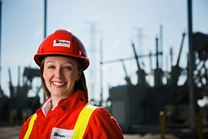 Image of Hydro Ottawa engineer with a transformer station in the background