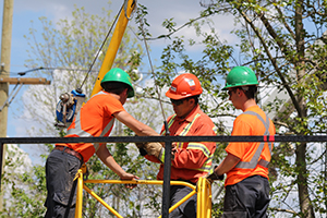 Image of two Powerline Maintainer apprentices with a Hydro Ottawa journeyman mentor
