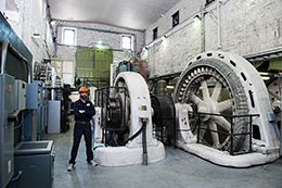 Image: Hydro Ottawa employee standing within a generating station at Chaudière Falls