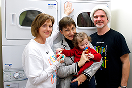 Photograph of Hydro Ottawa volunteers and Youville Centre's Executive Director in front of ENERGY STAR washers and dryers financed through the Brighter Tomorrows Fund