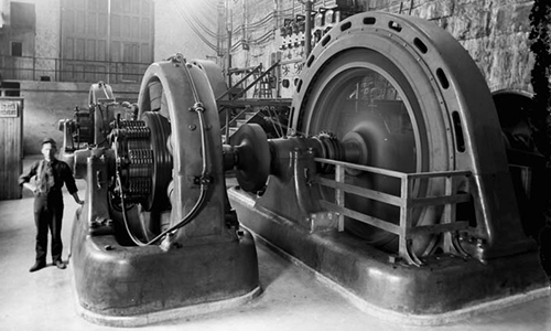 Ottawa Hydro employee standing beside turbines inside Generating Station No. 4 at Chaudière Falls. Date unknown.