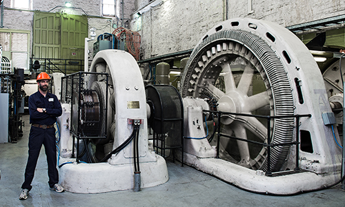 Hydro Ottawa employee standing beside refurbished turbines inside Generating Station No. 4 at Chaudière Falls. Ottawa 2014