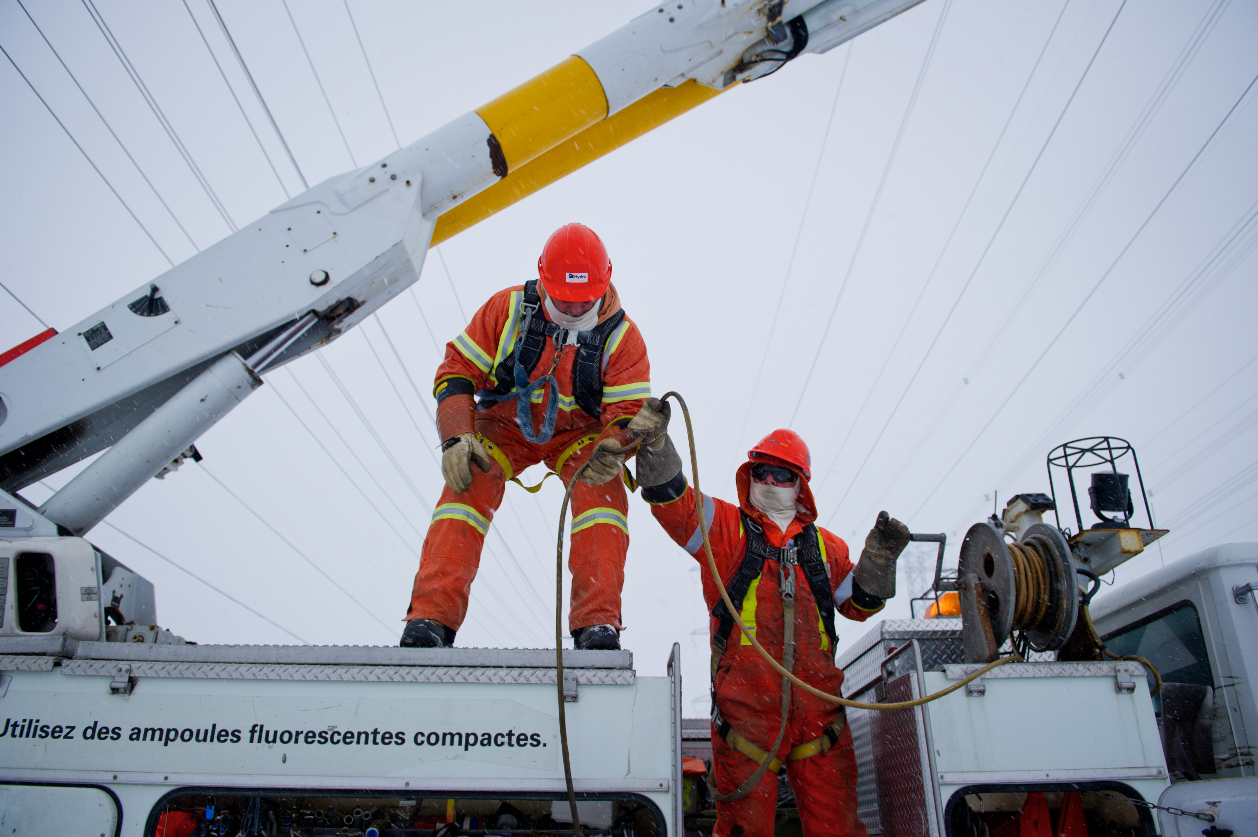 Two Hydro Ottawa Power Line Maintainers Working Outside On A Cold Winter Day