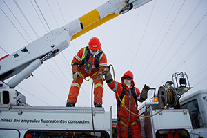 Two Hydro Ottawa power line maintainers working outside on a cold, winter day.