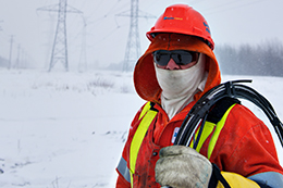 A Hydro Ottawa power line maintainer working outside on a cold, winter day.