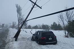 A damaged vehicle parked near a fallen hydro pole.