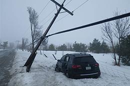 Un véhicule endommagé, stationné à proximité d'un poteau électrique tombé.