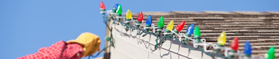 Une personne accrochant lumières de Noël sur le toit de leur maison.