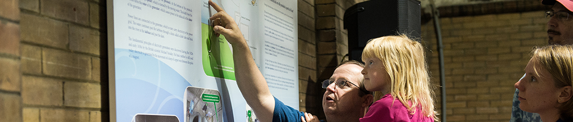 Photograph of a young girl and her father learning about electricity generation at Doors Open Ottawa