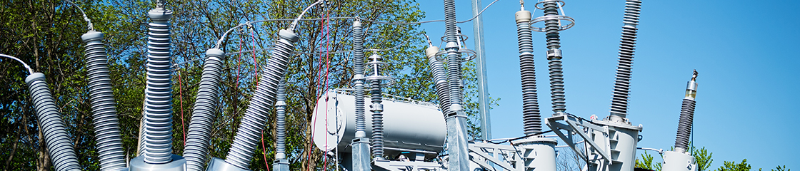 Close-up of transformer facility with insulators and electric wires