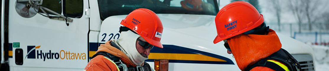 Deux employ�s � l'entretien des lignes �lectriques discutant d'un projet planifi� et camion � nacelle d'Hydro Ottawa en arri�re-plan
