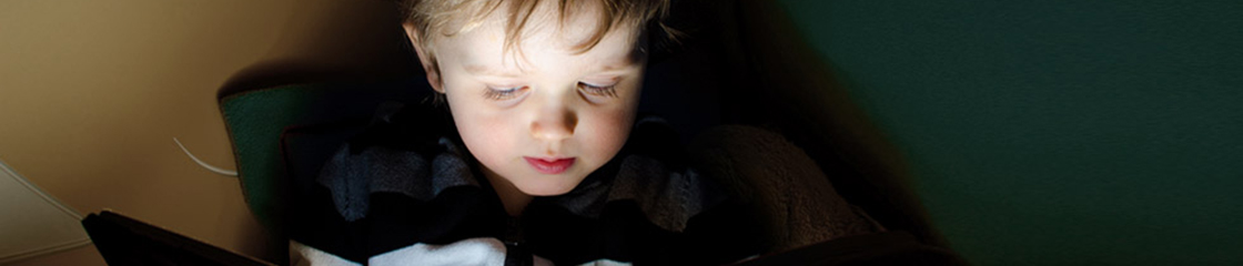A child looking at a tablet in a dark room
