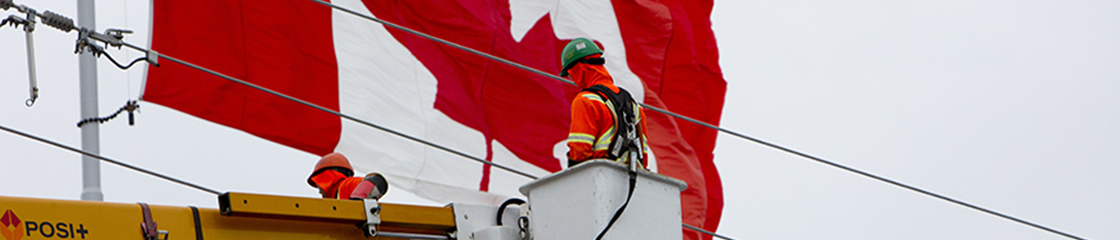 Hydro Ottawa's power line technician working with Canada's flag behind