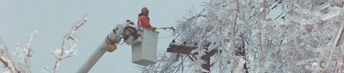 Photo of powerline maintainer in an aerial bucket surrounded by ice covered trees working to restore power in the aftermath of the 1998 Ice Storm.