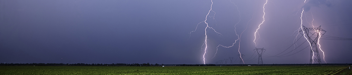 A thunderstorm with heavy lightning around powerlines in an open field