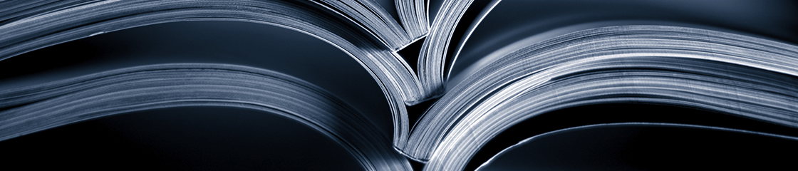 Close up of the spines of an open stack of books