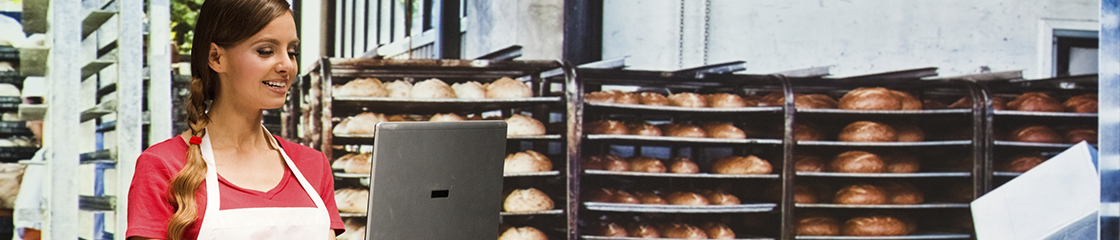 Small business owner working on a laptop with racks of freshly baked goods in the background
