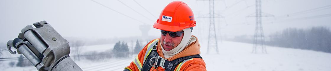 Un employé à l'entretien des lignes électriques d'Hydro Ottawa répare des lignes électriques lors d'une journée froide d'hiver