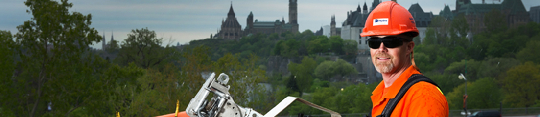 Powerline Maintainer working with Parliament Hill in the background