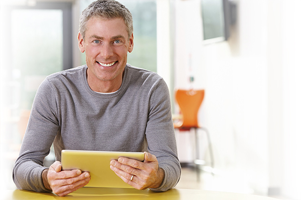 Smiling man holding a tablet FR