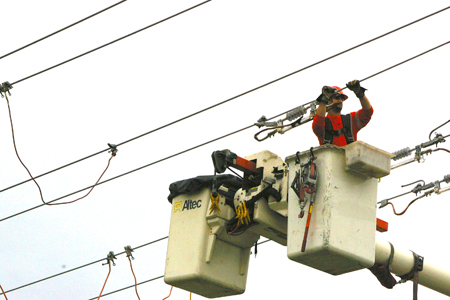 Linesperson suspended in bucket of a truck works on cables