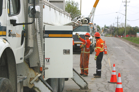 Workers discuss site plans beside a hydro bucket truck