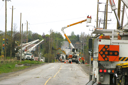 Bucket trucks and heavy equipment line Maple Grove Avenue where work is being done